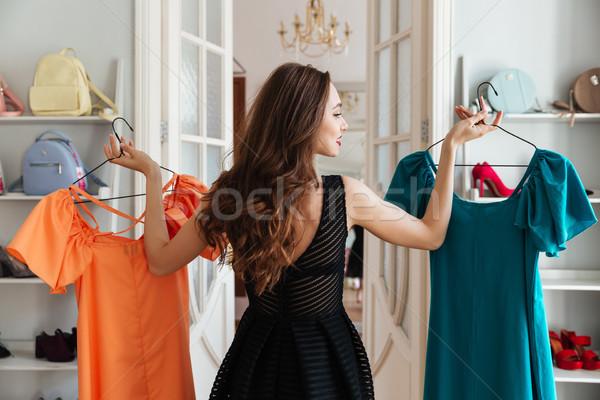 Jovem senhora em pé roupa compras escolher Foto stock © deandrobot