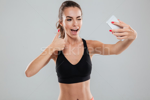 Szczęśliwy kobieta fitness smartphone kciuk Zdjęcia stock © deandrobot
