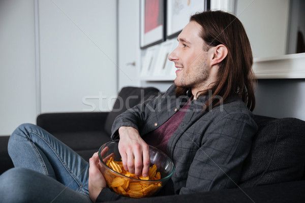 Man sitting at home indoors eating crisps Stock photo © deandrobot