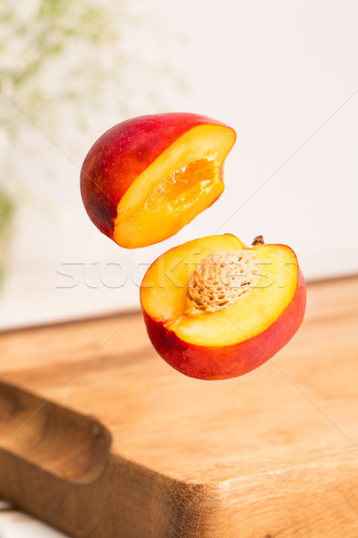 Close up of a sliced whole nectarine flying Stock photo © deandrobot