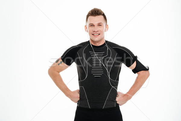 Portrait of a happy smiling man athlete in earphones standing Stock photo © deandrobot