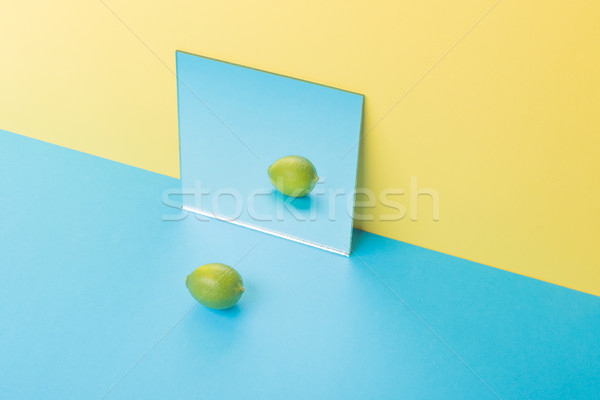 Lime on blue table isolated over yellow background near mirror Stock photo © deandrobot