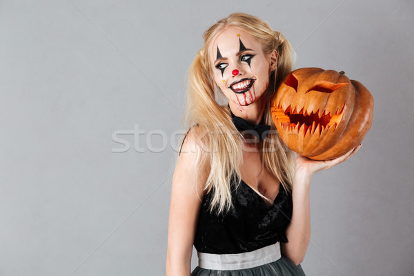 Stock photo: Smiling blonde woman in halloween make-up posing with carved pumpkin