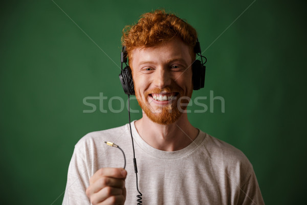 Close-up of young curly readhead hipster holding cord of headpho Stock photo © deandrobot