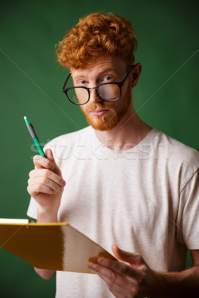 Smart readhead bearded man in white tshirt holding folder and pe Stock photo © deandrobot