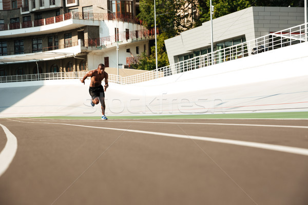 Photo of young african athlete man run on running track outdoors Stock photo © deandrobot