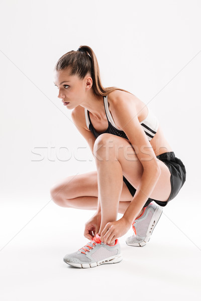 Young pretty fitness woman sitting and tying her shoelaces Stock photo © deandrobot