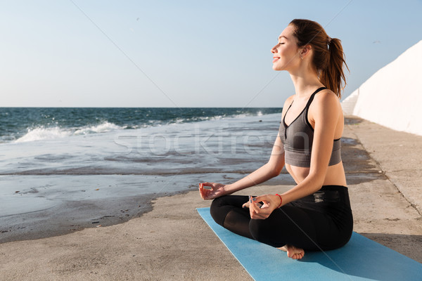 Portrait of cheerful brunette in sportwear sitting in lotos pose Stock photo © deandrobot