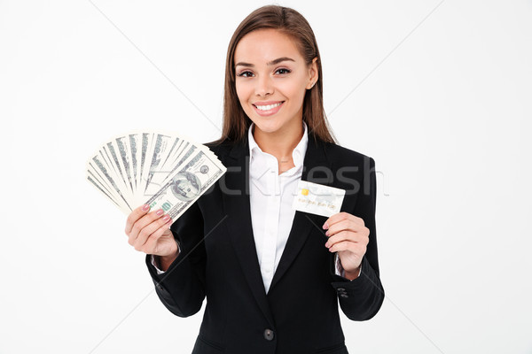 Cheerful pretty businesswoman holding money and credit card Stock photo © deandrobot