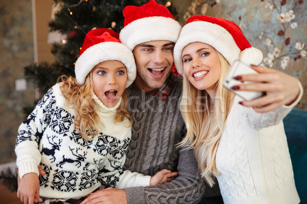 Funny young parents with those little daughter in Santa's hat ta Stock photo © deandrobot