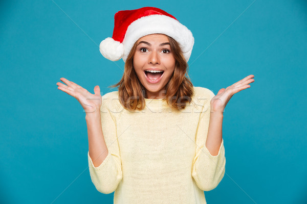 Surprised cheerful woman in sweater and christmas hat rejoice Stock photo © deandrobot