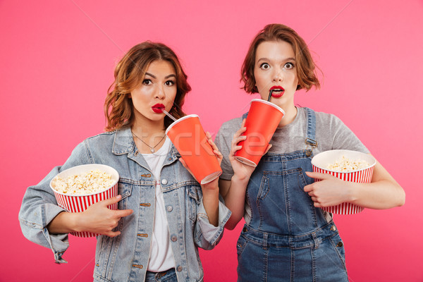 Shocked women friends eating popcorn watch film Stock photo © deandrobot