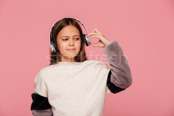 Fiatal elégedetlen lány lökés fejhallgató izolált Stock fotó © deandrobot
