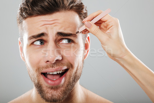 Female hand plucking scared men's eyebrows Stock photo © deandrobot
