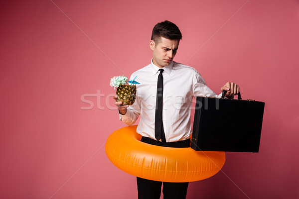 Displeased man looking at brief-case while holding cocktail Stock photo © deandrobot