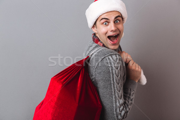 Side view of surprised man in sweater and christmas hat Stock photo © deandrobot