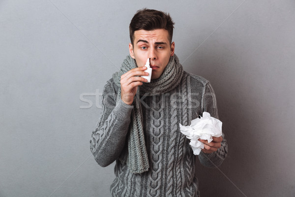Sick Man in sweater and scarf holding serviette Stock photo © deandrobot