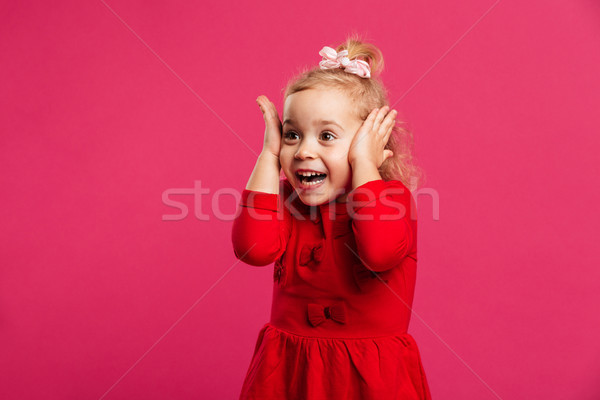 Surprised happy young girl in red dress holding her head Stock photo © deandrobot