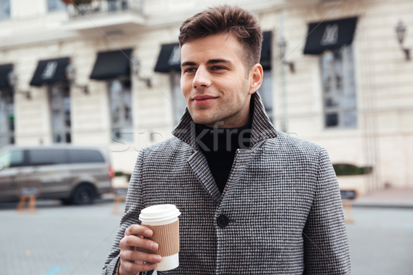 Picture of handsome man enjoying takeaway coffee from paper cup, Stock photo © deandrobot