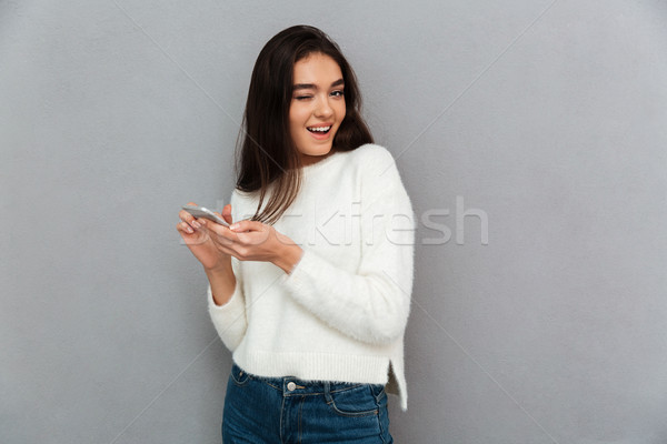 Close-up portrait of funny beautiful woman holding mobile phone  Stock photo © deandrobot