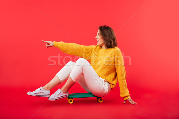 Portrait of a smiling girl sitting on a skateboard Stock photo © deandrobot