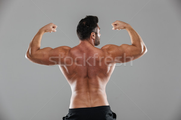 Back view portrait of a muscular male bodybuilder flexing muscles Stock photo © deandrobot