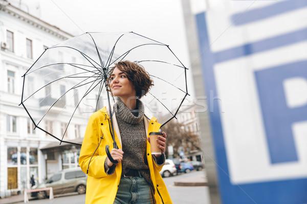 Elegáns nő citromsárga esőkabát sétál városi Stock fotó © deandrobot