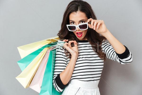 Portrait of a pretty flirty woman holding shopping bags Stock photo © deandrobot