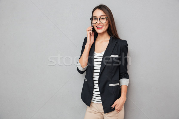 Pleased asian business woman in eyeglasses talking by smartphone Stock photo © deandrobot