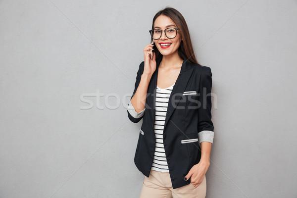 Soddisfatto asian donna d'affari parlando smartphone Foto d'archivio © deandrobot