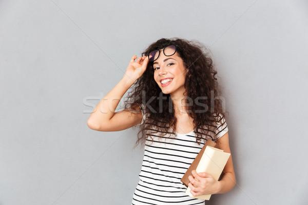 Genç kadın öğretmen gözlük kıvırcık saçlı ayakta Stok fotoğraf © deandrobot
