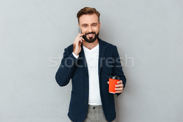 Smiling bearded man in business clothes talking by smartphone Stock photo © deandrobot