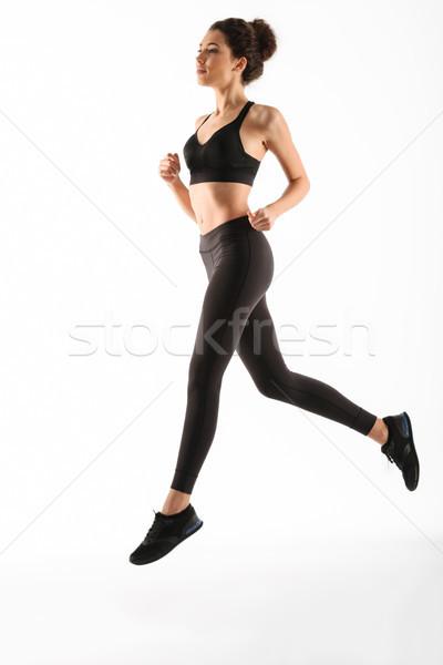 Stock photo: Full length image of Smiling fitness woman running in studio