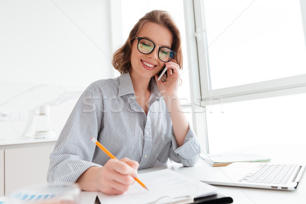 Beautiful smiling girl in glasses talking on mobile phone while  Stock photo © deandrobot