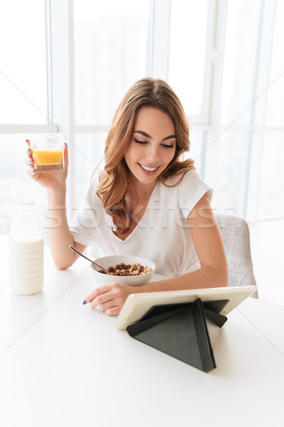 Pretty woman drinking juice using tablet computer. Stock photo © deandrobot