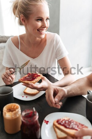 Stock photo: Happy woman looking at her man while they eating breakfast