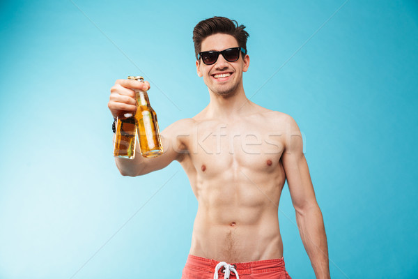 Portrait if a smiling shirtless man showing beer bottle Stock photo © deandrobot