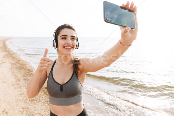 Cheerful young sportswoman standing at the beach Stock photo © deandrobot