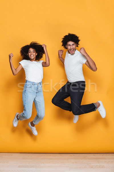 Full length portrait of a smiling young afro american couple Stock photo © deandrobot