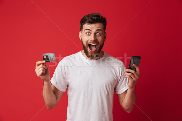 Excited screaming young man holding mobile phone and credit card. Looking camera. Stock photo © deandrobot