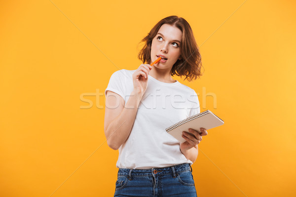 Thinking young woman writing notes. Looking aside. Stock photo © deandrobot