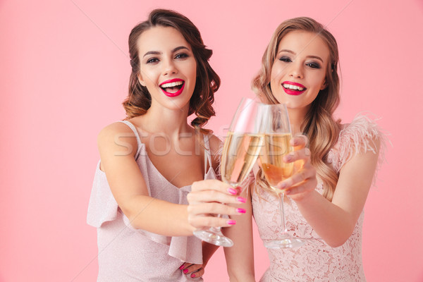 Two cheerful women in dresses drinking champagne Stock photo © deandrobot
