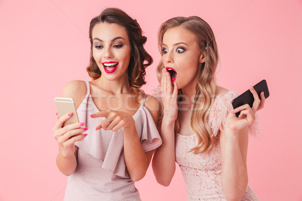 Stock photo: Two elegant women in dresses standing together and using smartphone