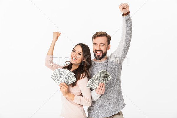 Happy young loving couple holding money make winner gesture Stock photo © deandrobot