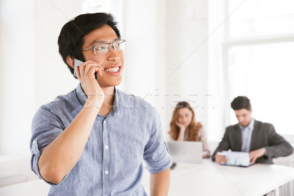 Stock photo: Happy young asian man talking on mobile phone