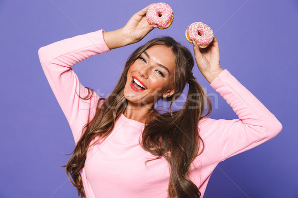 Stock photo: Portrait of a happy girl in sweatshirt posing with donuts