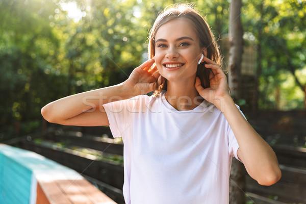 Mosolyog fiatal lány zenét hallgat fülhallgató park kint Stock fotó © deandrobot