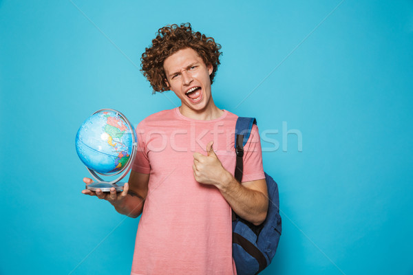 Portrait of joyful smarty guy with curly hair wearing backpack h Stock photo © deandrobot