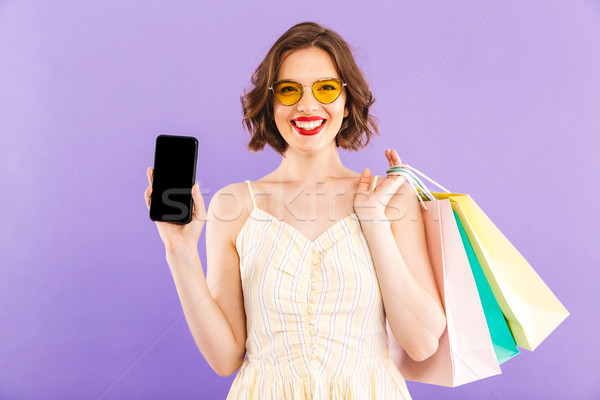 Woman isolated over purple wall showing display of mobile phone. Stock photo © deandrobot