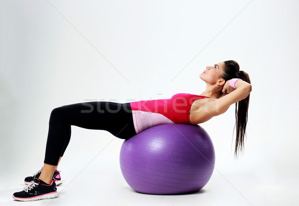 Young sport woman doing abs workout on fitball over gray background Stock photo © deandrobot